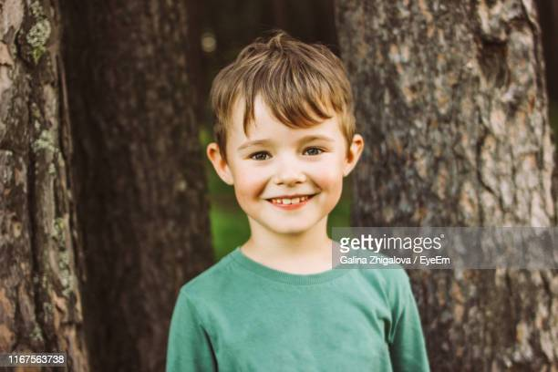 portrait of cute boy looking away standing against tree trunk - sorriso aberto imagens e fotografias de stock