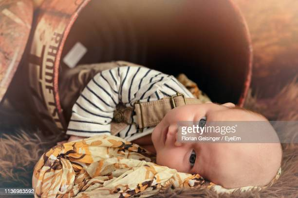 portrait of cute boy lying in metal drum - drum container stock photos and pictures