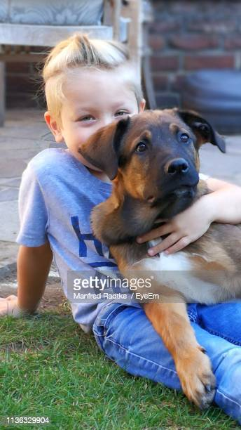 Portrait Of Cute Boy Playing With Dog On Grass