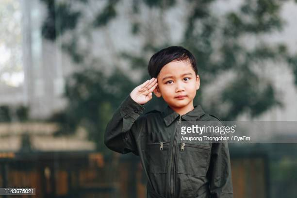 portrait of cute boy saluting while standing outdoors - saluting stock pictures, royalty-free photos & images