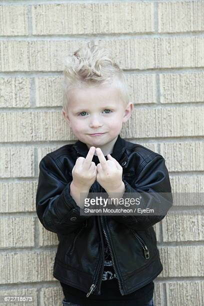 portrait of cute boy showing middle finger against brick wall - kid middle finger stock pictures, royalty-free photos & images