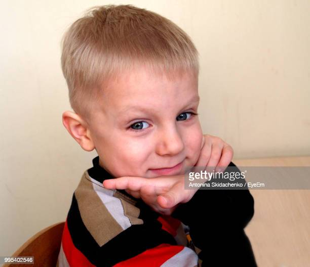 Portrait Of Cute Boy Sitting At Table In Home