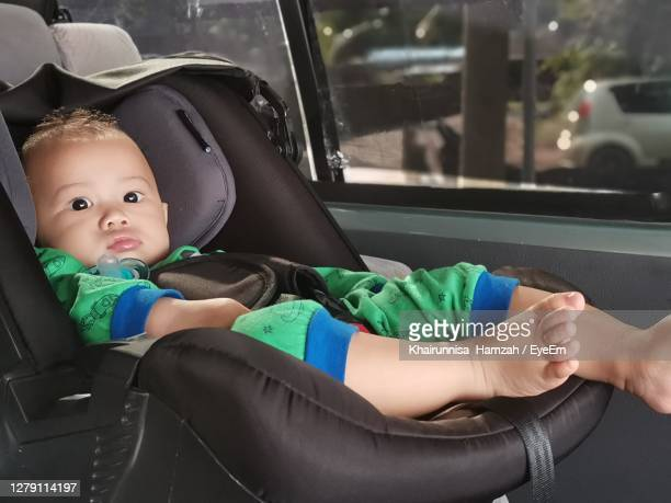 portrait of cute boy sitting in car - one baby boy only stock pictures, royalty-free photos & images