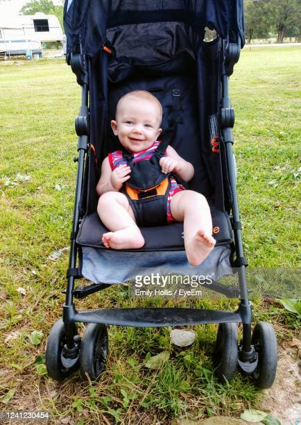 portrait of cute boy sitting in park - one baby boy only stock pictures, royalty-free photos & images