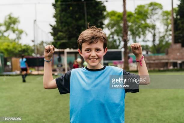 porträt eines niedlichen jungen, der auf dem fußballplatz steht - trikot stock-fotos und bilder