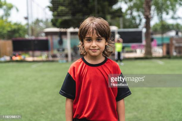 portrait of cute boy standing on soccer field - boys stock pictures, royalty-free photos & images