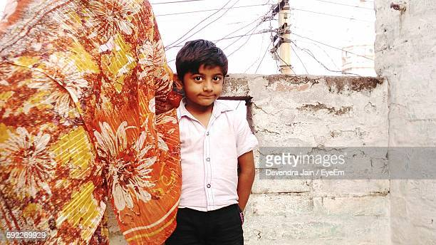 Portrait Of Cute Boy Standing With Mother