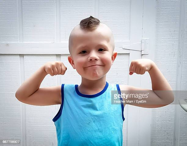portrait of cute boy with a double biceps pose - mohawk stock photos and pictures