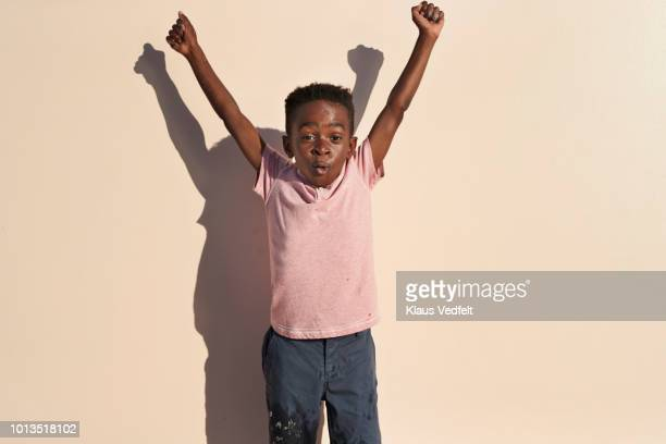 portrait of cute boy with arms in the air on studio backdrop - vreugde stockfoto's en -beelden