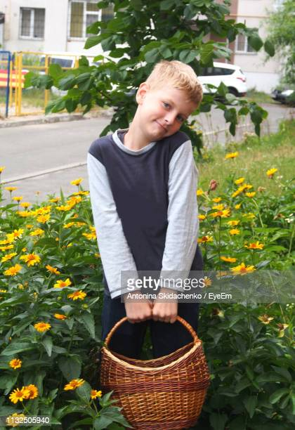 Portrait Of Cute Boy With Basket Standing On Field