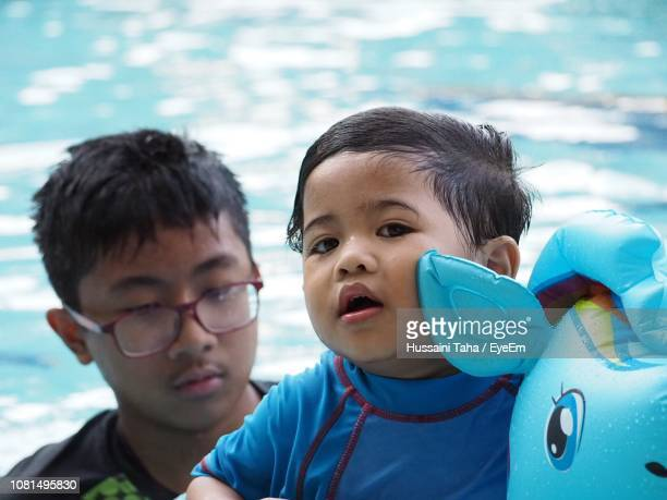 Portrait Of Cute Boy With Brother In Swimming Pool