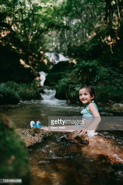 Portrait of cute Eurasian little girl playing in river water in forest