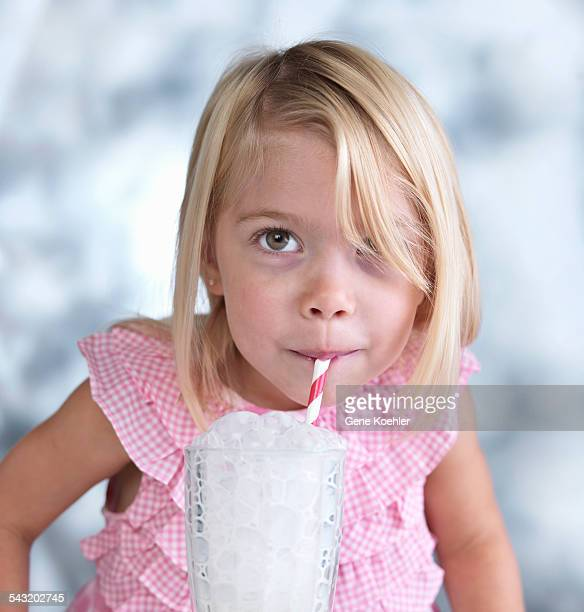 portrait of cute female toddler blowing bubbles in glass of milk - kitchen utensil stock pictures, royalty-free photos & images
