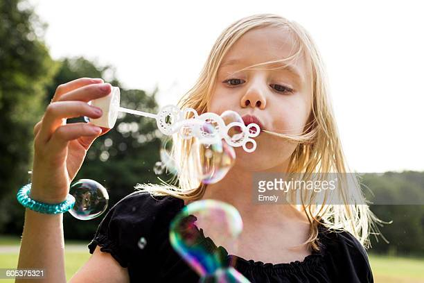 Portrait of cute girl blowing bubbles in park