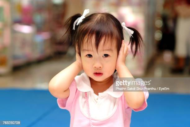 Portrait Of Cute Girl Covering Ears While Standing In Room