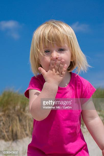 portrait of cute girl covering mouth with hand against sky - fehmarn stock pictures, royalty-free photos & images