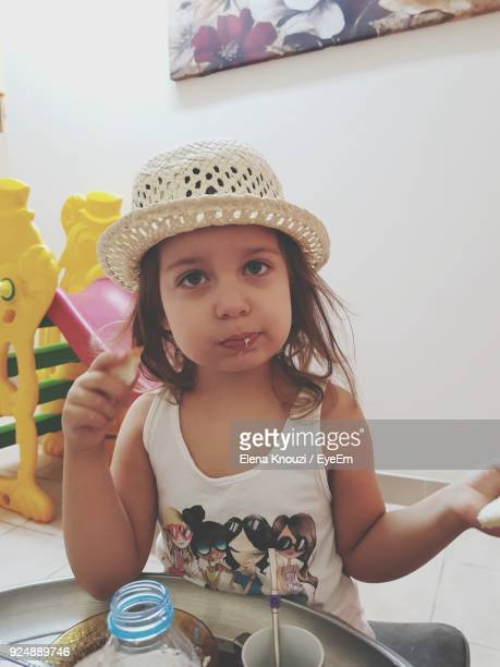 portrait of cute girl eating food while sitting at home - elena knouzi stock pictures, royalty-free photos & images
