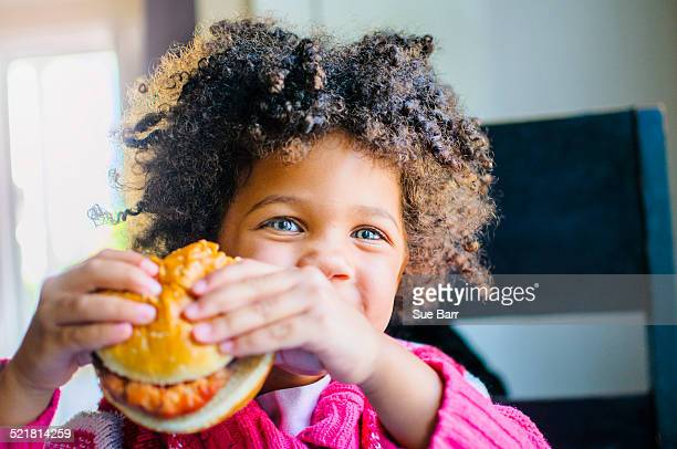 Portrait of cute girl eating hamburger in kitchen