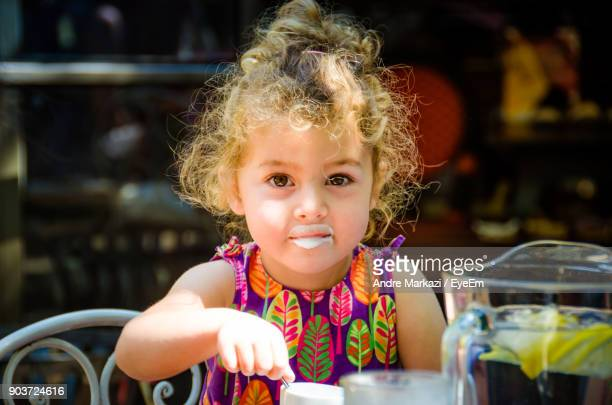 Portrait Of Cute Girl Eating While Sitting At Cafe