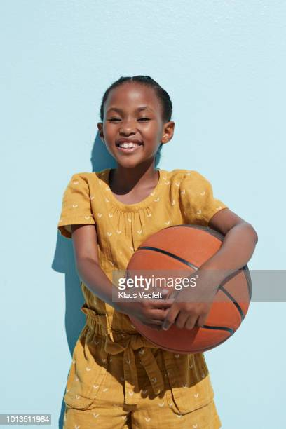 portrait of cute girl holding basketball and laughing - black photos et images de collection