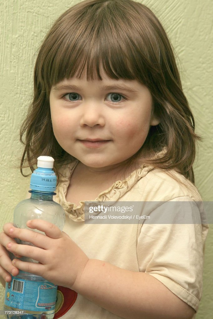 Portrait Of Cute Girl Holding Bottle Against Wall : Photo