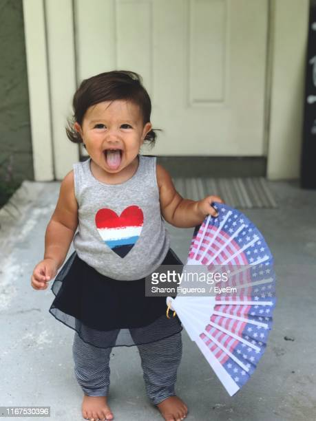 portrait of cute girl holding folding fan while standing at home - innocence fotografías e imágenes de stock