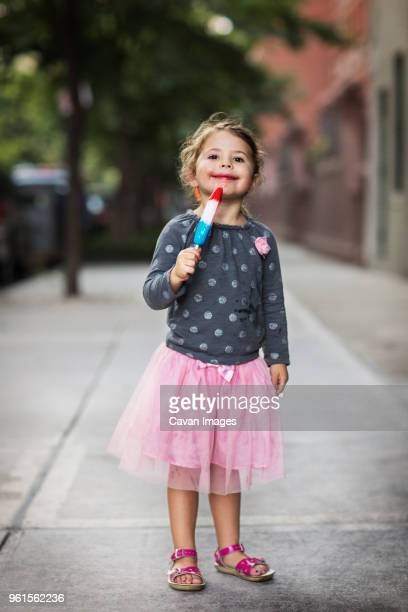 Portrait of cute girl holding ice lolly on footpath