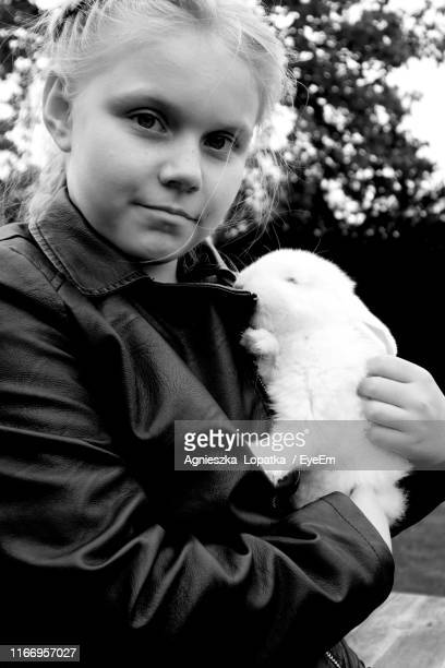 Portrait Of Cute Girl Holding Rabbit While Standing Outdoors