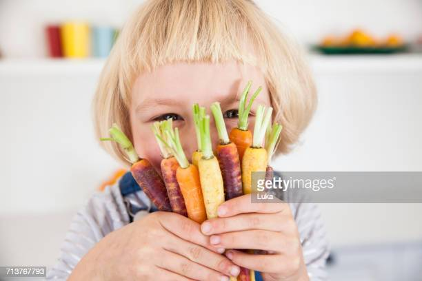 Portrait of cute girl in kitchen holding bunch of colourful carrots to her face