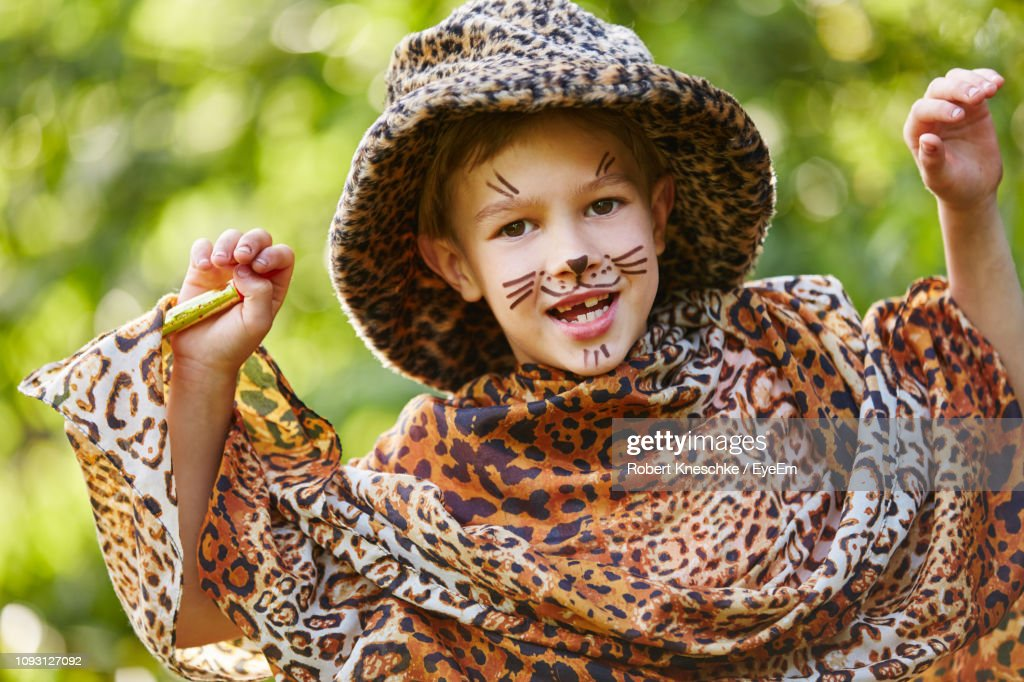 44cdd1c10cb4 Portrait Of Cute Girl In Leopard Costume Gesturing While Standing In Yard :  Stock Photo