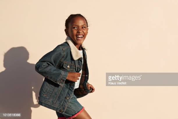 portrait of cute girl laughing, on studio background - veste noire photos et images de collection