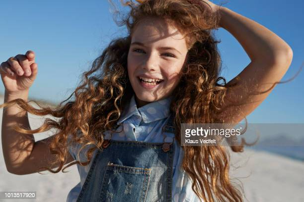 portrait of cute girl laughing with blue sky in background - innocenza foto e immagini stock