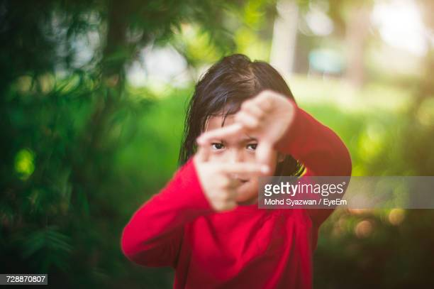 portrait of cute girl making frame with hands - malaysia beautiful girl stock photos and pictures