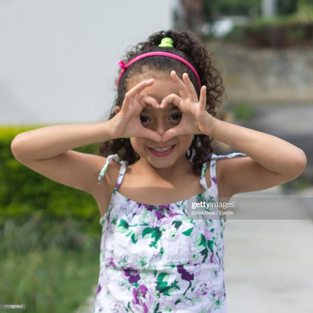 Portrait Of Cute Girl Making Heart Shape With Hands Stock Photo ...