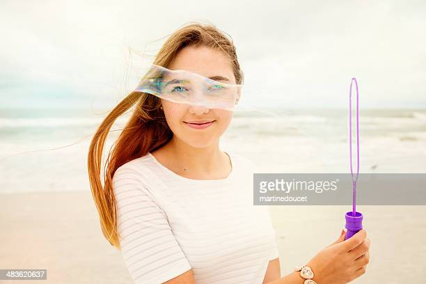 Portrait of cute girl making soap bubbles on the beach.