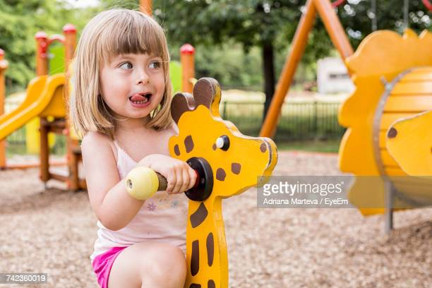portrait of cute girl playing at playground - free images for educational use stock pictures, royalty-free photos & images