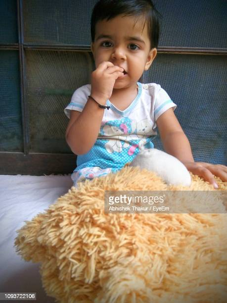 Portrait Of Cute Girl Playing With Teddy Bear At Home