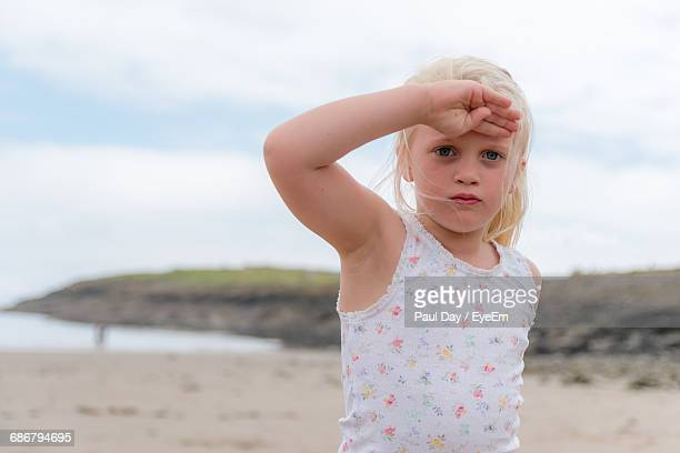 portrait of cute girl saluting at beach - saluting stock pictures, royalty-free photos & images