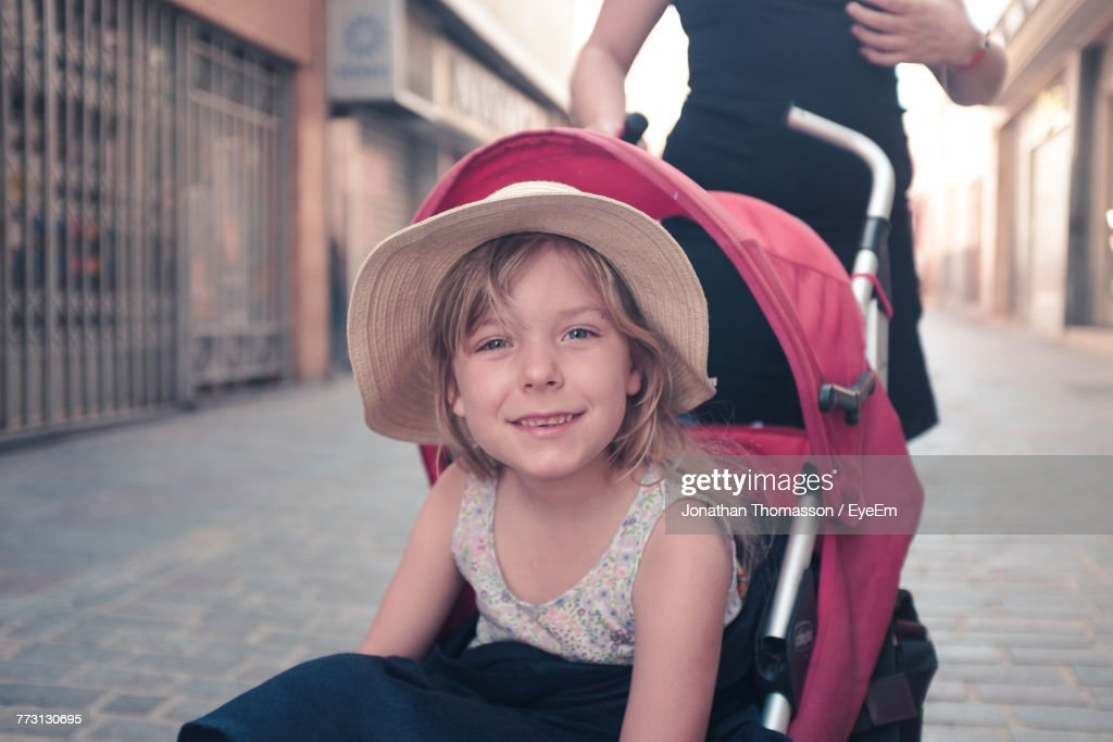 Portrait Of Cute Girl Sitting In Baby Carriage : Photo