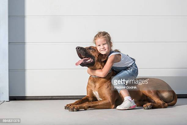 Portrait of cute girl sitting on dog outdoors