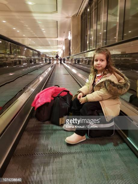 portrait of cute girl sitting on escalator - elena knouzi stock pictures, royalty-free photos & images