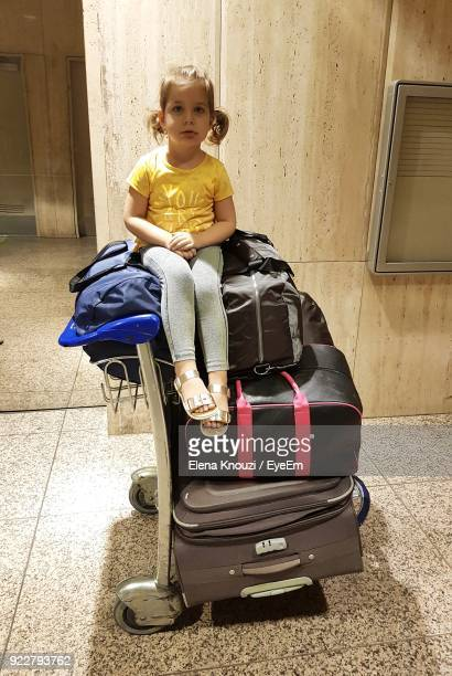 portrait of cute girl sitting on luggage at home - elena knouzi stock pictures, royalty-free photos & images
