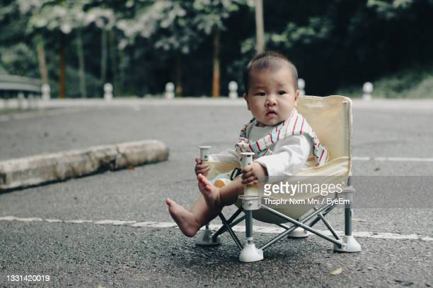 portrait of cute girl sitting on road - unknown gender stock pictures, royalty-free photos & images