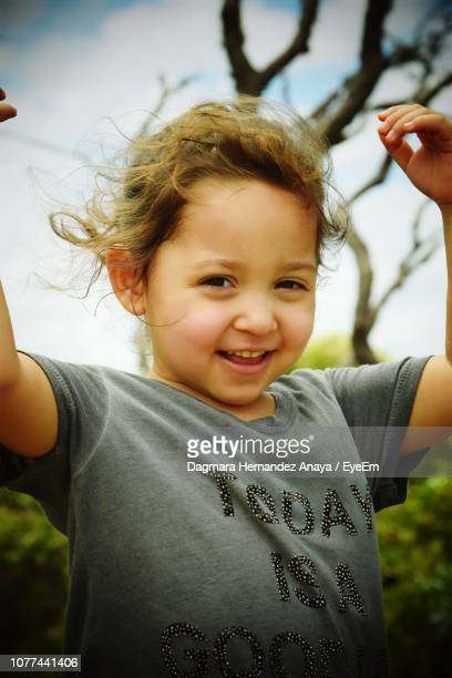 Portrait Of Cute Girl Smiling Against Sky