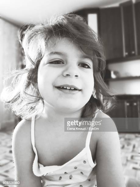 portrait of cute girl smiling on bed at home - elena knouzi stock pictures, royalty-free photos & images