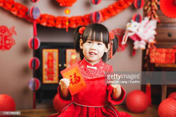 portrait of cute girl standing against decorations at home - fringe dress stock pictures, royalty-free photos & images