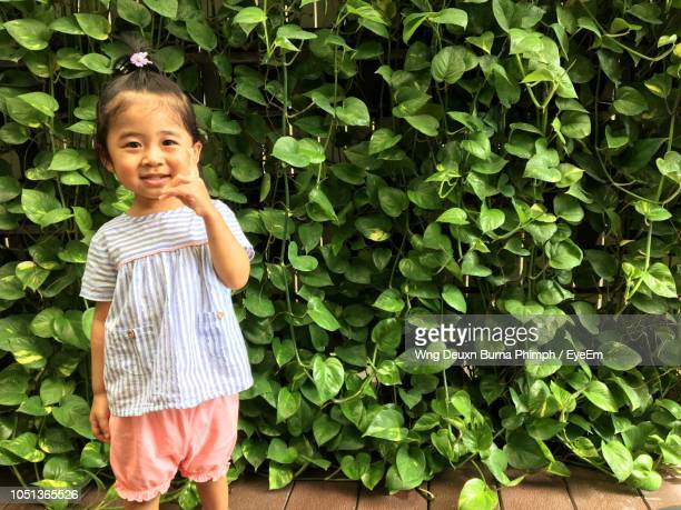 Portrait Of Cute Girl Standing Against Plants