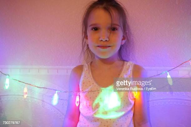 Portrait Of Cute Girl Standing By Illuminated String Lights At Home