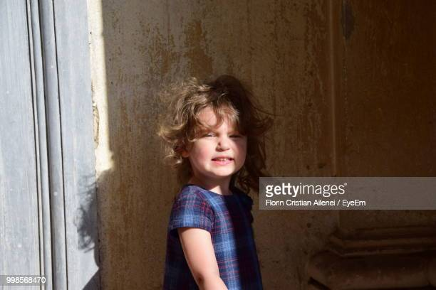 Portrait Of Cute Girl Standing By Wall
