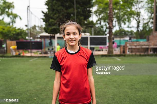 portrait of cute girl standing on soccer field - sports jersey stock pictures, royalty-free photos & images